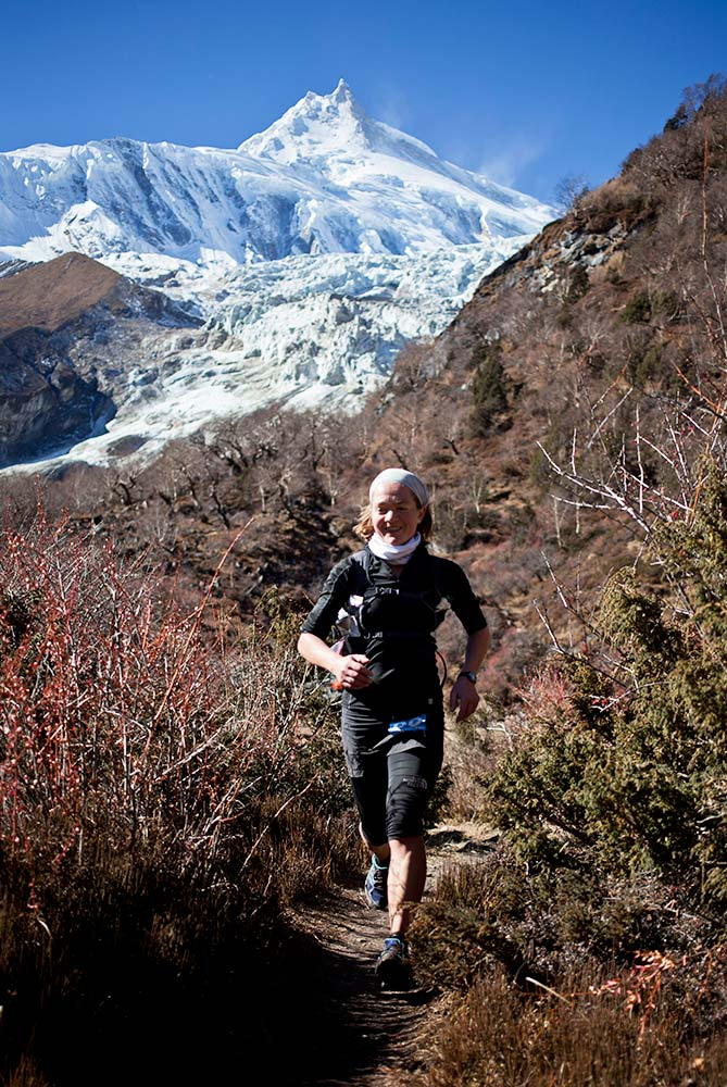 Lizzy Hawker running with Manaslu basecamp behind